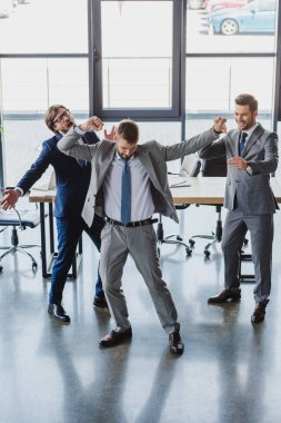 excited young businessmen dancing and celebrating in office