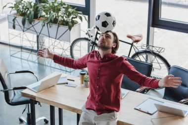 high angle view of young businessman balancing soccer ball on head in office