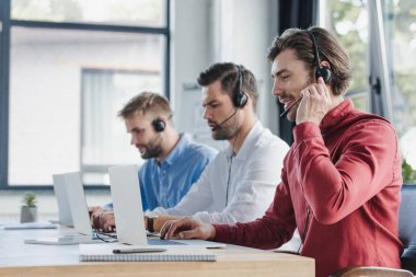 Three young call center operators in headsets using laptops in office stock vector