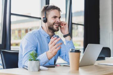 smiling young call center operator in headset working with laptop in office