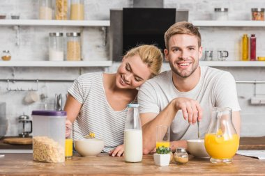happy couple sitting at table with milk, juice and cornflakes in kitchen