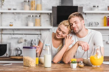 couple having breakfast and hugging with closed eyes in kitchen