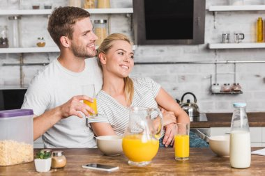 happy boyfriend hugging girlfriend during breakfast and holding glass of juice in kitchen