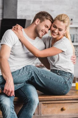 happy couple cuddling and sitting on kitchen counter