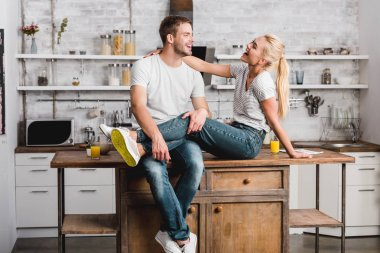 laughing couple hugging and sitting on kitchen counter