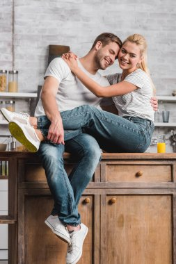 happy couple hugging and sitting on kitchen counter