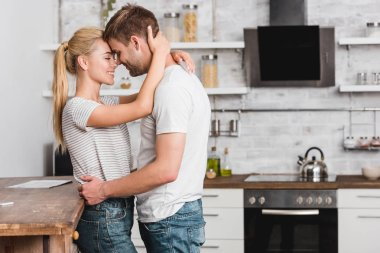 side view of couple cuddling in kitchen and leaning on kitchen counter