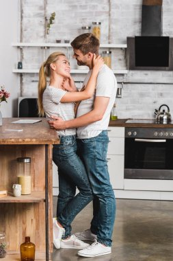 Side view of couple hugging in kitchen and leaning on kitchen counter stock vector