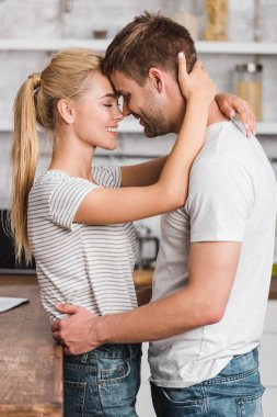 side view of happy couple hugging in kitchen