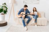 mladý pár ladění akustická kytara s digitálním tabletu na gauči doma