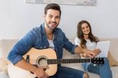 usmívající se muž ladění kytary a při pohledu na fotoaparát a jeho přítelkyně, sedí poblíž s digitálním tabletu na gauči doma