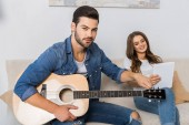 jistý muž, ladění kytara a při pohledu na fotoaparát a jeho přítelkyně, sedí poblíž s digitálním tabletu na gauči doma