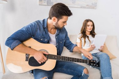 handsome man tuning guitar while his girlfriend sitting near with digital tablet on sofa at home