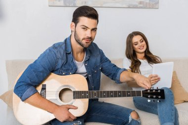 confident man tuning guitar and looking at camera while his girlfriend sitting near with digital tablet on sofa at home