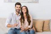 boldog fiatal pár pohár pezsgőt pihent a kanapén, otthon portréja