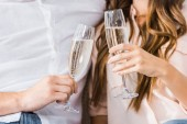 Fotografie beschnitten, Schuss paar klirrende Gläser Champagner auf Sofa im neuen Zuhause