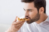 portrait of young man eating pizza alone at home