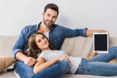 smiling woman showing digital tablet with blank screen while her boyfriend sitting near on couch at home
