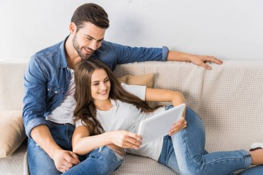 Happy young couple watching digital tablet on couch at home stock vector