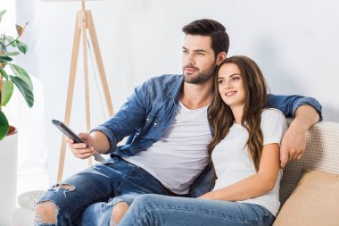 young couple with remote controller watching tv on couch at home
