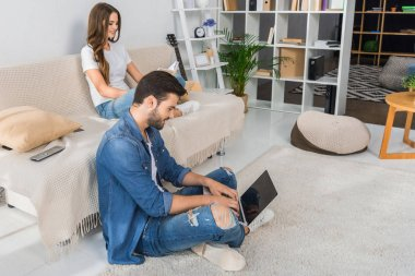 Side view of smiling man using laptop and sitting on floor while his girlfriend reading book on couch at home stock vector
