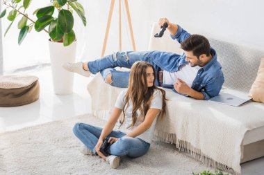 young man threatening by joystick to smiling girlfriend sitting on floor at home