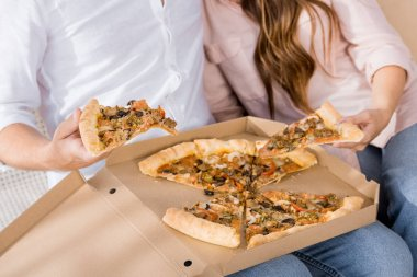 cropped shot of couple with pizza in paper box at home