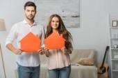 portrét usmívající se pár papír domy v rukou v novém domově