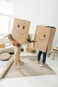 Fotografia vista oscurata di coppia con scatole di cartone su teste che tengono le mani a new house, casa concetto commovente
