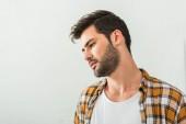 Fotografie portrét zamyšlený mladík koukal s šedou zdí na pozadí