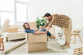 Seitenansicht des Paares, das Spaß mit Pappschachtel am neuen Haus hat, Umzugskonzept