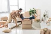 Seitenansicht des Paares Spaß mit Karton im neuen Haus, Umzug Wohnkonzept