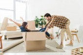 Photo side view of couple having fun with cardboard box at new house, moving home concept