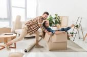 boční pohled na usmívající se pár baví s krabici v novém domě, stěhování domů concept