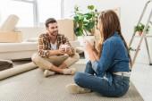 mladý pár s šálky kávy sedí na podlaze v novém domě, přesun domů concept