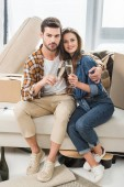 Photo couple in love clinking glasses of champagne at new house with cardboard boxes, moving home concept