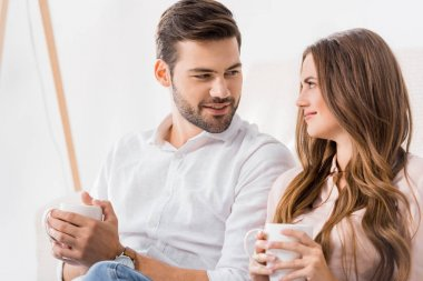 portrait of young loving couple with cups of coffee at home