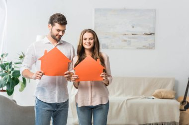portrait of smiling couple showing paper houses in hands at new home