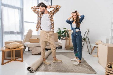 confused young couple at new house with cardboard boxes, moving home concept