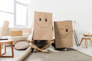 Obscured view of couple with cardboard boxes on heads sitting on floor at new house, moving home concept stock vector