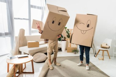 Obscured view of couple with cardboard boxes on heads at new house, moving home concept stock vector