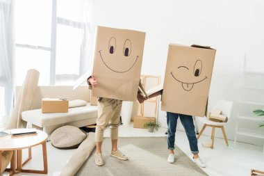 obscured view of couple with cardboard boxes on heads holding hands at new house, moving home concept