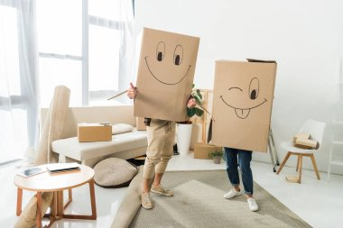 obscured view of couple with cardboard boxes on heads at new house, moving home concept