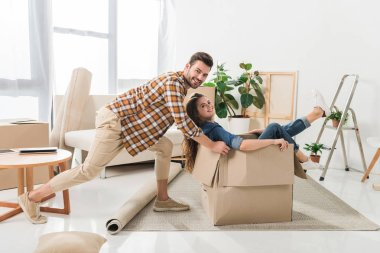Side view of smiling couple having fun with cardboard box at new house, moving home concept stock vector