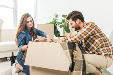 smiling couple unpacking cardboard boxes together at new home, moving home concept