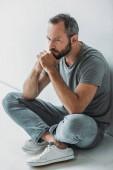 vysoký úhel pohled smutně vousatý muž sedí v patře a koukal