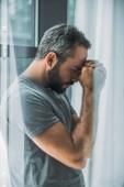 Fotografia vista laterale del depresso frustrato uomo barbuto in piedi vicino alla finestra