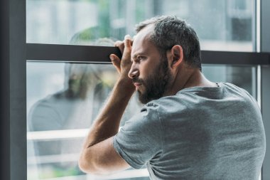 upset bearded man leaning at window and looking through it