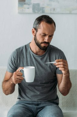sick bearded middle aged man holding cup and looking at thermometer