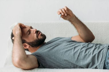 sick bearded man lying on couch and holding thermometer